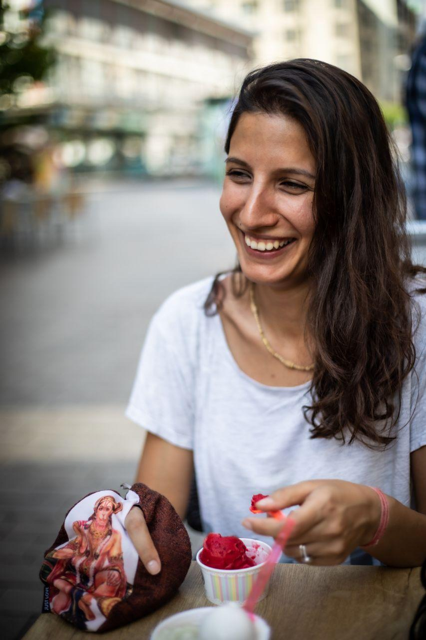 woman eating pink sorbet smiling and chanting mantra on mala in a bag